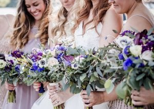 group of bridesmaids holding purple flowers